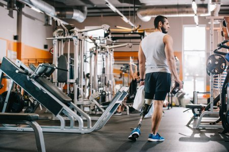 handsome young sportsman with artificial leg standing at gym and holding towel
