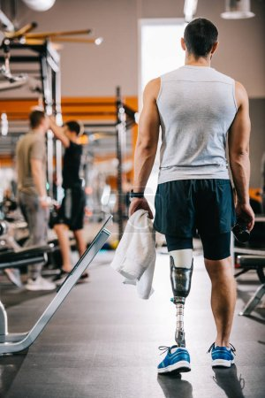 rear view of sportsman with artificial leg standing at gym and holding towel