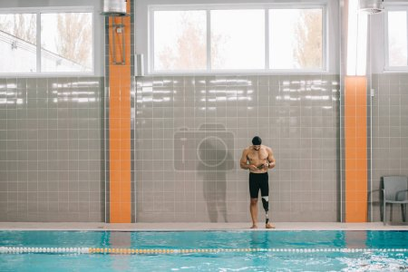 beau jeune sportif avec jambe artificielle debout au bord de la piscine intérieure