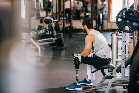 Photo for Overworked sportsman with artificial leg sitting at gym - Royalty Free Image