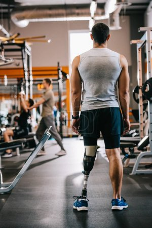 Photo for Rear view of sportsman with artificial leg standing at gym - Royalty Free Image