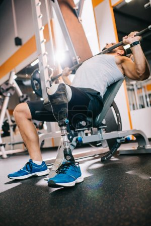 athletic young sportsman with artificial leg lifting barbell at gym