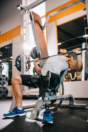 fit young sportsman with artificial leg lifting barbell at gym