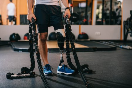 cropped shot of sportsman with artificial leg working out with ropes at gym