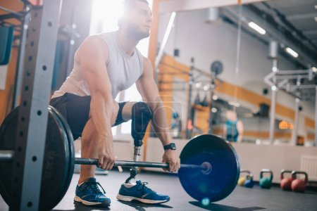 attractive young sportsman with artificial leg working out with barbell at gym