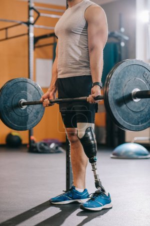 cropped shot of muscular sportsman with artificial leg working out with barbell at gym