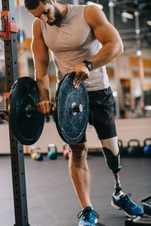handsome young sportsman with artificial leg preparing for workout with barbell at gym
