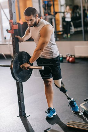 athletic young sportsman with artificial leg preparing for workout with barbell at gym