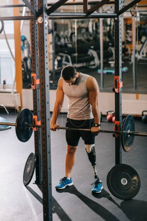 athletic young sportsman with artificial leg working out with barbell at gym