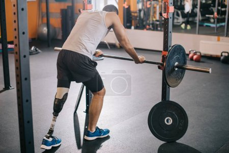 Photo for Handsome young sportsman with artificial leg leaning on barbell at gym - Royalty Free Image