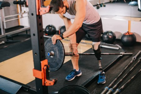 Photo for Handsome young sportsman with artificial leg putting on weight plate on bar at gym before workout - Royalty Free Image