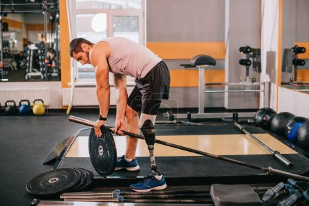 handsome young sportsman with artificial leg putting on weight plate on bar at gym