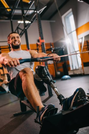 muscular young sportsman with artificial leg working out with rowing machine at gym