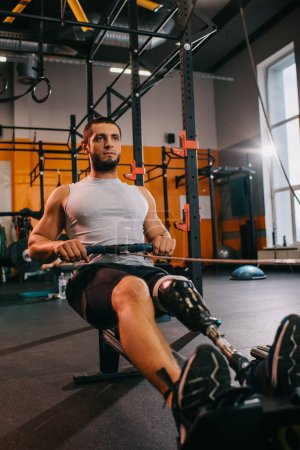 athletic young sportsman with artificial leg working out with rowing machine at gym