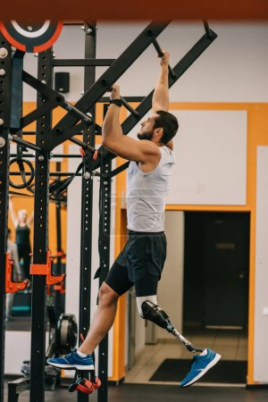 handsome young sportsman with artificial leg working out with gymnastics ladder at gym