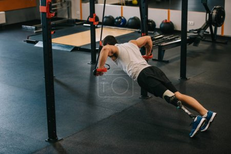 handsome young sportsman with artificial leg doing push ups with hanging rings of gymnastics ladder at gym