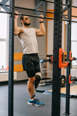 handsome young sportsman with artificial leg doing bul ups at gym