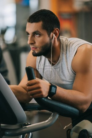 handsome young man working out on stationary bicycle at gym