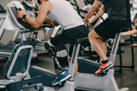 sportsman with artificial leg working out on stationary bicycle at gym