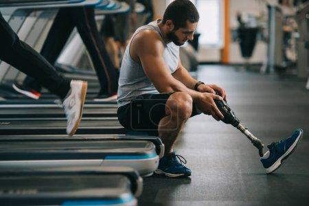 Photo pour Vue latérale d'épuisé jeune sportif avec une jambe artificielle assis sur le tapis roulant à la gym - image libre de droit