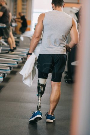rear view of sportsman with artificial leg walking by gym