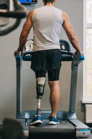 rear view of young sportsman with artificial leg walking on treadmill at gym