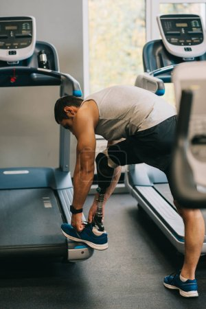 young sportsman with artificial leg lacing up shoe at gym