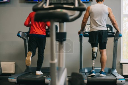 rear view of sportsmen running on treadmills at gym