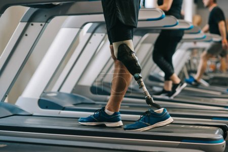 cropped shot of man with artificial leg walking on treadmills at gym with other people