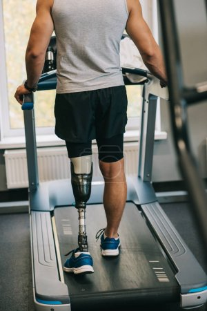 cropped shot of sportsman with artificial leg walking on treadmill at gym