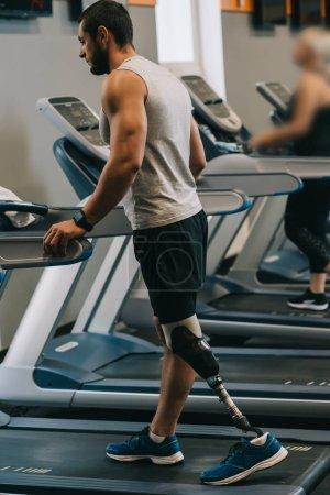 beau jeune sportif avec jambe artificielle marche sur treadmilsl à la salle de gym