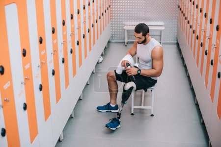 Photo for Handsome young sportsman with artificial leg sitting on bench at gym changing room - Royalty Free Image