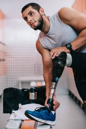 Photo for Fit young sportsman with artificial leg preparing for training at gym changing room - Royalty Free Image