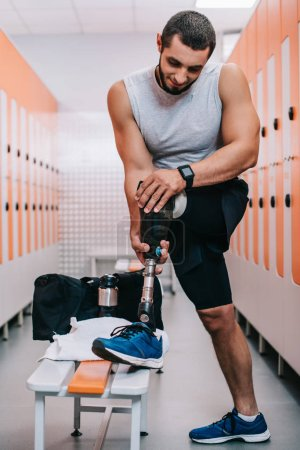 Photo for Athletic young sportsman putting on artificial leg at gym changing room - Royalty Free Image