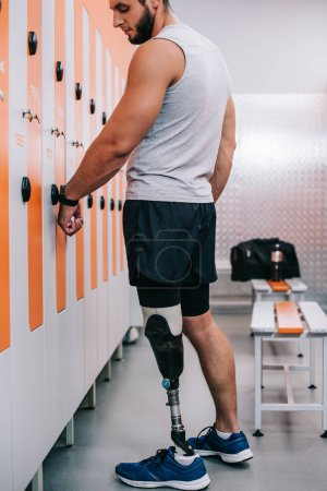 handsome young sportsman with artificial leg opening locker with electric key on his wrist at gym changing room