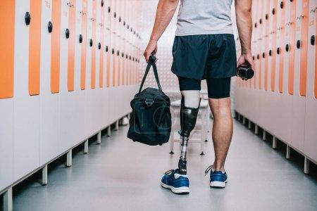 Photo pour Recadrée tir sportif avec debout jambe artificielle au vestiaire de gym avec bouteille de remise en forme et sac - image libre de droit