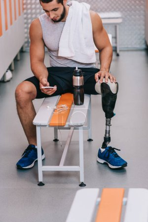 attractive young sportsman with artificial leg sitting on bench at gym changing room and using smartphone