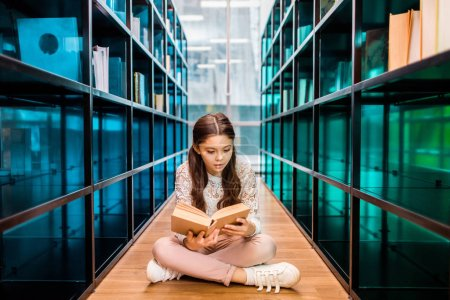 Photo for Adorable concentrated schoolgirl reading book on floor in library - Royalty Free Image