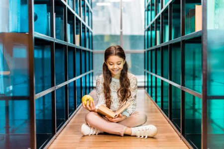 Photo for Beautiful happy schoolchild holding apple and reading book in library - Royalty Free Image