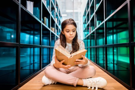 Photo for Adorable focused schoolgirl sitting on floor and reading book in library - Royalty Free Image