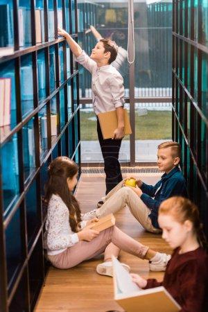 Photo pour Vue grand angle d'adorables écoliers lisant des livres dans la bibliothèque - image libre de droit