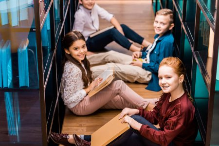 high angle view of classmates with books sitting on floor and smiling at camera in library