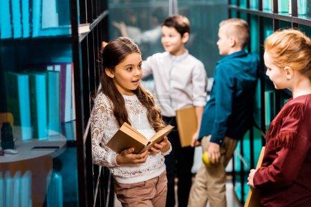 Photo pour Beaux écoliers tenant des livres et parlant dans la bibliothèque - image libre de droit