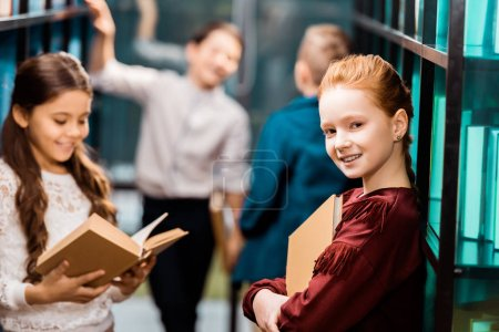 Photo for Beautiful schoolchild holding book and smiling at camera while visiting library with classmates - Royalty Free Image