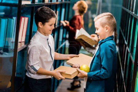 Photo for Side view of cute smiling schoolkids holding books and apple in library - Royalty Free Image