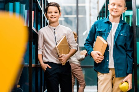 Photo for Adorable schoolboys holding books and smiling at camera in library - Royalty Free Image