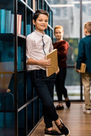 Photo pour Écolier tenant le livre et souriant à la caméra tout en visitant la bibliothèque avec des camarades de classe - image libre de droit