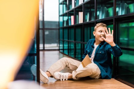 smiling schoolboy holding book and waving hand while sitting on floor in library