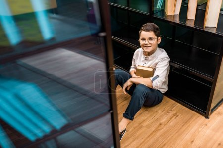 high angle view of schoolboy in eyeglasses holding book and smiling at camera in library