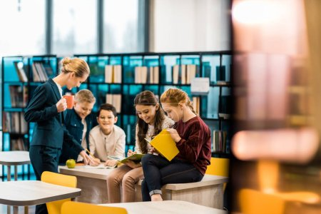 Photo for Selective focus of schoolchildren and librarian reading books together in library - Royalty Free Image